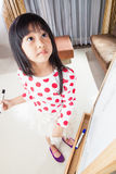 Kid girl writes on a white board with black mark pen. Royalty Free Stock Image