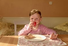 Kid girll eats chocolate cream spread on bread. Chocolate sweet food snack. Happy girl has a snack in the kitchen. A. Cute small girl smiles. A small girl with Stock Photos