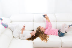 Kid girls having fun playing with tablet pc lying sofa Stock Photos