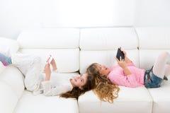 Kid girls having fun playing with tablet pc lying sofa Royalty Free Stock Photo