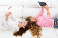 Kid girls having fun playing with tablet pc lying sofa Royalty Free Stock Images
