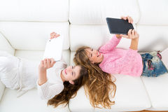 Kid girls having fun playing with tablet pc lying sofa Royalty Free Stock Photography