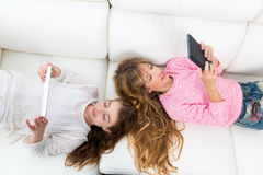 Kid girls having fun playing with tablet pc lying sofa Stock Image