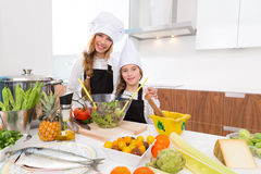 Kid girls junior chef friends hug together in countertop Royalty Free Stock Photos