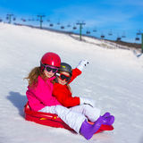 Kid girls playing sled in winter snow. With helmets and goggles Stock Photos