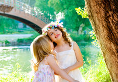 Kid girls playing in spring outdoor river park. Whispering ear Stock Photos