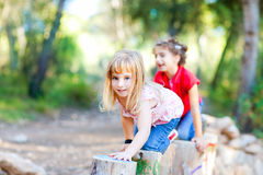 Kid girls playing on trunks in forest nature. Kid girls playing on trunks knee walking in forest nature Stock Image