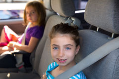 Kid girls with safety belt in car indoor Stock Image