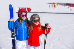 Kid girls sister in winter snow with ski equipment Royalty Free Stock Photography
