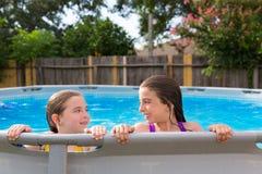 Kid girls swimming in the pool in backyard Stock Photos