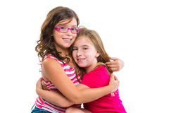 Kid girls tender hug smiling ans friends cousins. On white background royalty free stock photography
