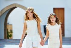 Kid girls walking hand in hand Mediterranean village Stock Photos