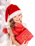 Kid giving Christmas gift box. Child in Santa hat giving gift box near white Christmas tree. Isolated Royalty Free Stock Image