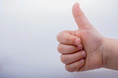 kid giving  thumb up as a symbol and like icon Royalty Free Stock Image