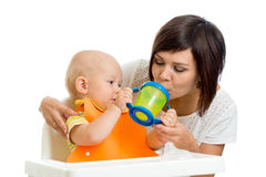 Kid giving to mom water from his feeding cup Royalty Free Stock Image