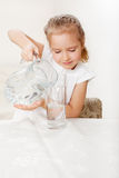 Kid with glass pitcher water. Child with glass pitcher water. Little girl drinking water at home Royalty Free Stock Images