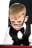 Kid in glasses. Child in white shirt and bow tie looks in laptop Stock Photography