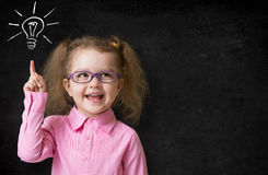 Kid in glasses with idea lamp on school chalkboard Royalty Free Stock Photos