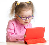 Kid in glasses looking at mini tablet pc screen at table Royalty Free Stock Images