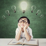 Kid with glasses thinking idea under lamps Stock Photos