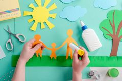 Kid is gluing paper shape stock image