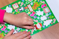 Kid is gluing a sticker on applique.  Stock Images
