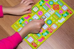 Kid is gluing a sticker on applique.  Royalty Free Stock Photo