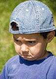 Kid godfather. A angry kid with strong expression on his face, false mustache and hat on the head Stock Images