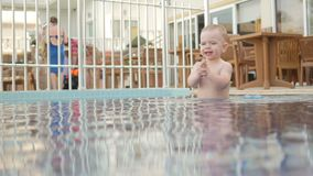 The Kid goes around the children`s pool on the street. He enjoys water and plays with drops. stock video footage