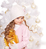 Kid with gold Christmas gift box. Royalty Free Stock Image