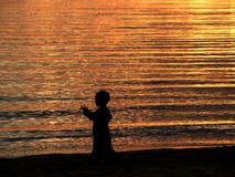 Kid and the golden sea. A little boy was waking at the beach. Sun was drifting into the golden sea. And everything was so beautiful Stock Photography