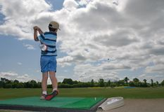 Kid Golfing. Young boy on the driving range just after power drive, with ball in midair; motion blur on the golf club Stock Photography