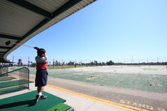 Kid at the golfing range. A little boy swinging at a golfing range Royalty Free Stock Image