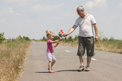 Kid and grandfather on the road Stock Photos