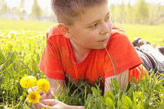 Kid on grass with dandelions looking sideways. Kid in orange shirt laying down on grass holding dandelions looking sideways Royalty Free Stock Photo