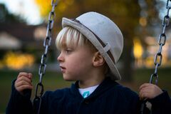 Kid in Gray Round Hat on Hanging Swing Stock Images