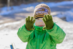 The kid in the green jacket on the street in winter Stock Images