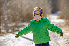 The kid in the green jacket on the street in winter Stock Photo