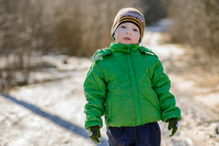 The kid in the green jacket on the street in winter Stock Image