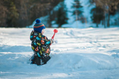 The kid in the green jacket on the street in winter Stock Photos