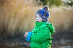 The kid in the green jacket in the winter. On the street Royalty Free Stock Photography