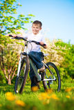 Kid in a green park on a bike Royalty Free Stock Photos