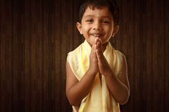 A kid greets with folded hands Royalty Free Stock Images