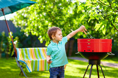 Kid grilling food on backyard party Royalty Free Stock Photo