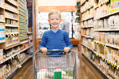 Kid at grocery store. Smiling little boy proud to do grocery shopping alone Stock Photography
