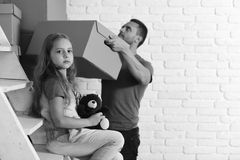 Kid and guy move in or out. Girl and man. Kid and guy move in or move out. Girl and men with busy and sad faces on white wall background, defocused. New home and Royalty Free Stock Photos