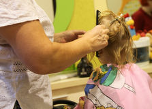 Kid by hairstylist. Hairdresser with comb combing hair of little girl Stock Photos