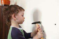 Kid hammering plastic anchor Stock Image