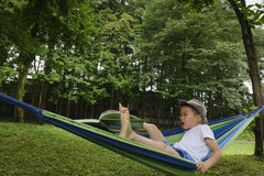 Awkward kid on hammock with book away Royalty Free Stock Photos