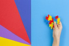 Kid hand holding colorful heart on multicolored background. World autism awareness day concept.  royalty free stock photography